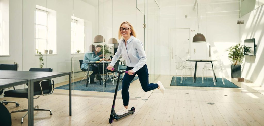 Office supply company having fun in the office with woman on a scooter